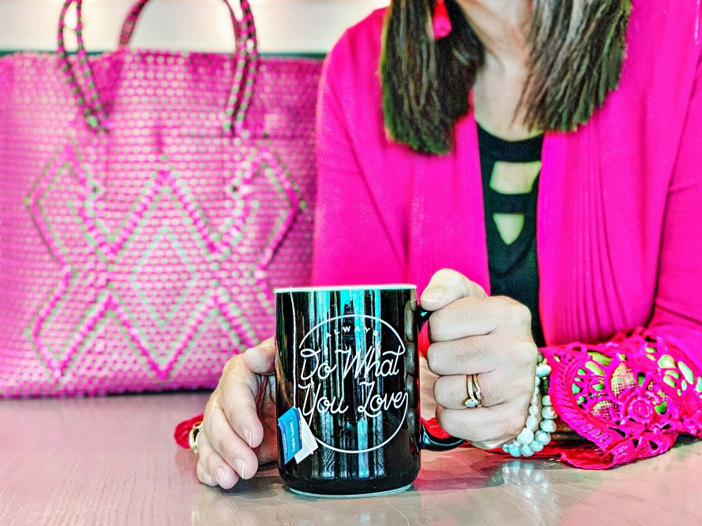 Carol Culver sitting with Do What You Love mug.